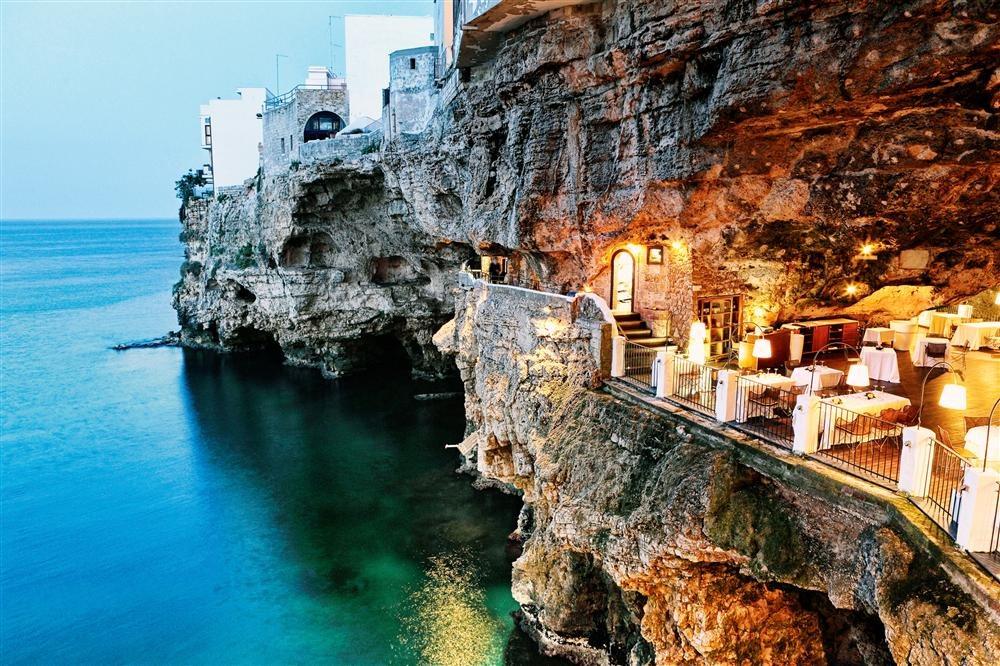 77037191. Polignano a Mare se asoma al mar desde un acantilado con numerosas grutas