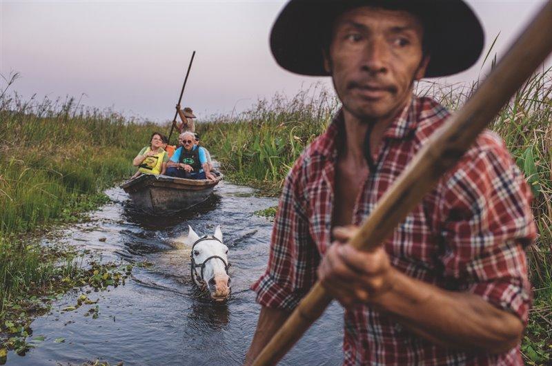 Seguido por la montura sobre la que más tarde cabalgará hasta su casa, Mingo Ávalos impulsa su canoa por un canal mientras otro guía y él dan un tour a unos turistas de visita en el Iberá. Todos ganan con el turismo: los antiguos cazadores y los que trabajan en la ganadería, como Ávalos, encuentran empleos respetuosos con el medio ambiente.