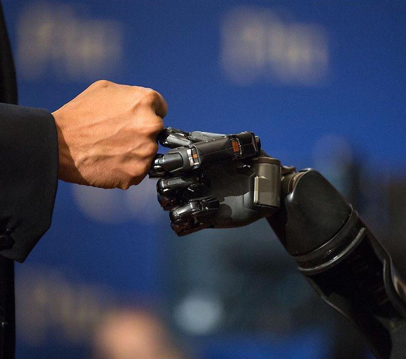 Nathan Copeland choca los nudillos de la mano robótica con el expresidente de Estados Unidos Barack Obama durante una visita a la Casa Blanca.