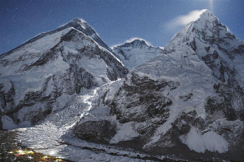 Las luces del Campo Base cintilan al pie del Everest mientras las lámparas frontales de los escaladores forman una senda luminosa, revelando su ascenso a través de la cascada de hielo del Khumbu, que entraña menor peligro de madrugada, cuando la temperatura cae por debajo del punto de congelación.