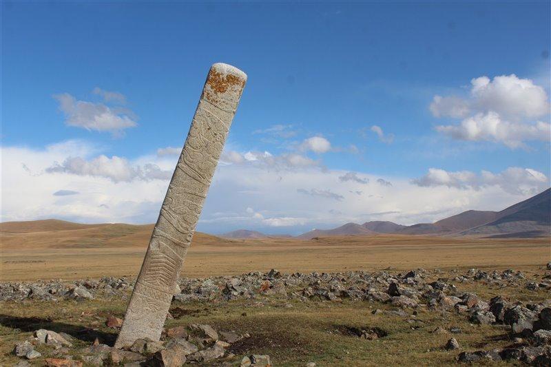 Piedra de ciervo inclinada colocada frente a docenas de pequeños montículos de piedra en cuyo interior se enterraron caballos sacrificados según un antiguo ritual.