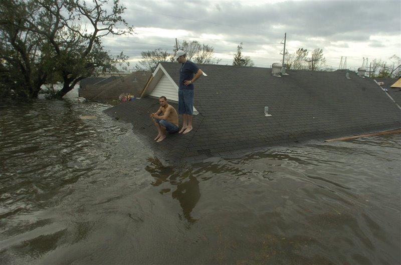 Dos hombres esperan ser rescatados en el tejado de la parroquia de su barrio en agosto de 2005.