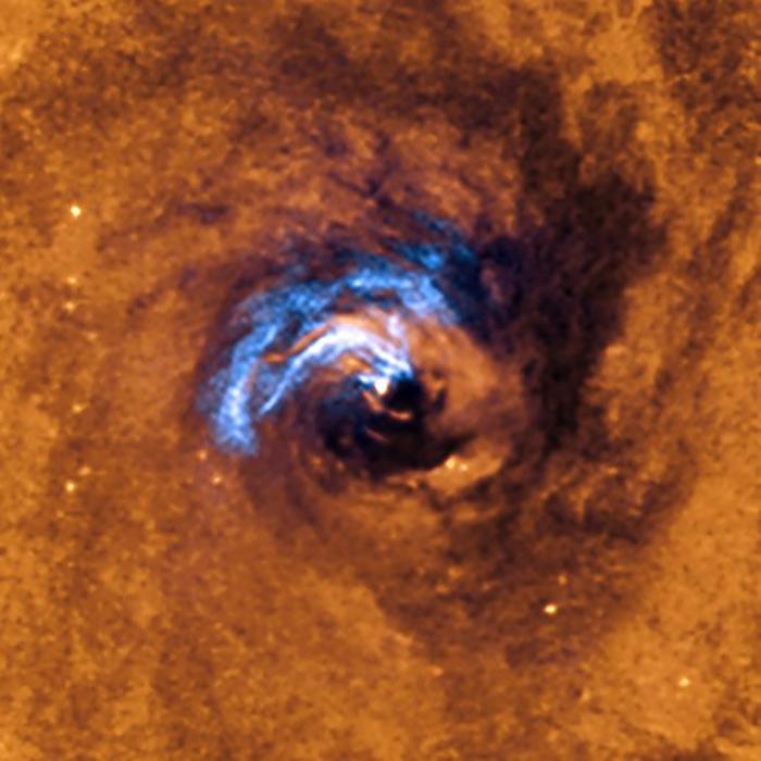 Esta imagen muestra el proceso de alimentación nuclear de un agujero negro en la galaxia NGC 1566, y cómo los filamentos de polvo, que rodean al núcleo activo, quedan atrapados y giran en espiral alrededor del agujero negro hasta que este se los traga.